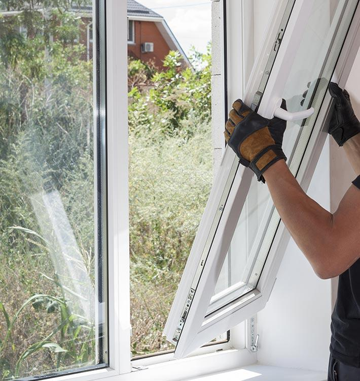 Professional worker repairs double glazing windows