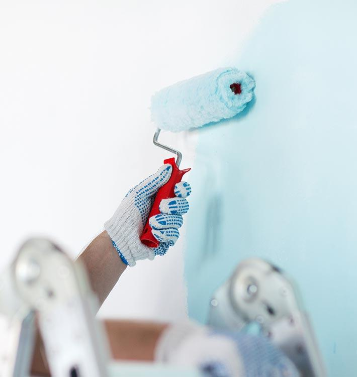 Decorators in home painting wall